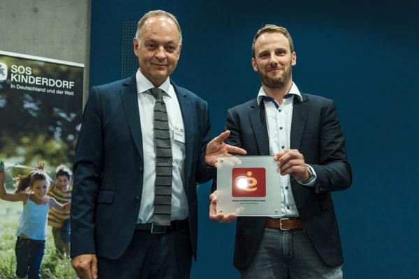 Timo Witt, Vorsitzender Verbund der Embrace Hotels e.V., überreicht Wolfgang Graßl, Geschäftsführer des Hotel Rossi der Botschaft für Kinder gGmbH, die offizielle Embrace-Plakette